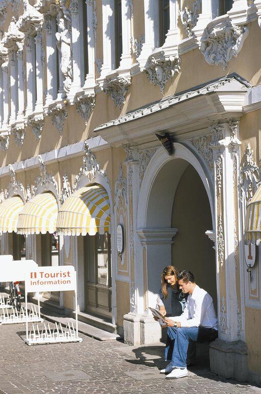 Touristenpaar mit Stadtplan vor dem Falkenhaus in Würzburg