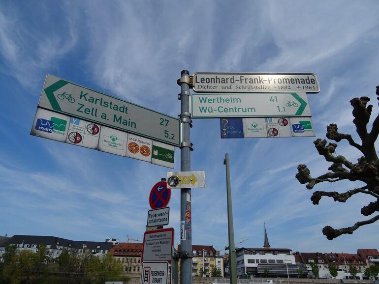 Bild eines Hauptwegweisers mit Fern- und Nahzielen als auch eingeschobenen Plaketten von touristischen Themenradwegen.