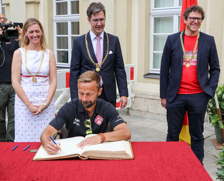 Großer Anteil am Erfolg: Trainer Michael Schiele trägt sich ins Goldene Buch ein.